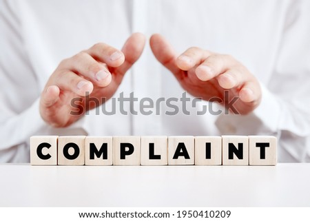 Businessman holding his hands over the wooden cubes with the word complaint. Customer complaints support or care concept. Photo stock ©