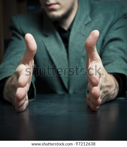 """Businessman holding his hands to show """"this long/short"""""""