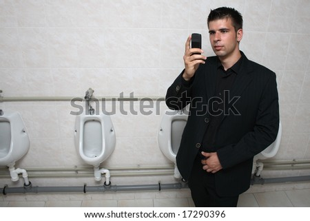 Businessman holding his mobile phone in a toilet, taking picture of himself.