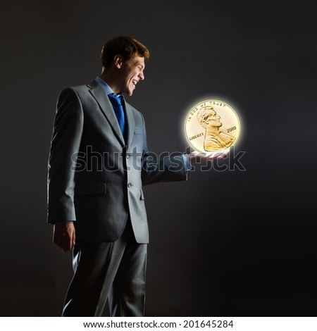 Businessman holding huge cent coin in hand