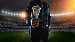 businessman holding large amount of bills at Soccer stadium in background