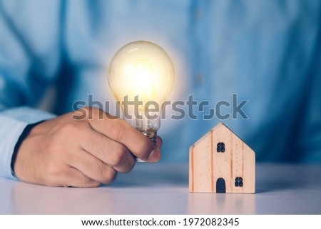 Businessman holding light bulb while home wooden for solution innovation and environment, thinking idea for planning buy house, residential with eco and saving energy, business and finance concept. Imagine de stoc ©