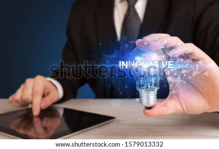 Businessman holding light bulb with INNOVATIVE inscription, innovative technology concept
