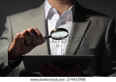 Businessman holding magnifying glass and digital tablet concept for internet search, job search or analysing accounts