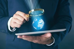 Businessman holding magnifying glass and tablet. Digital earth on screen. Technology concept.