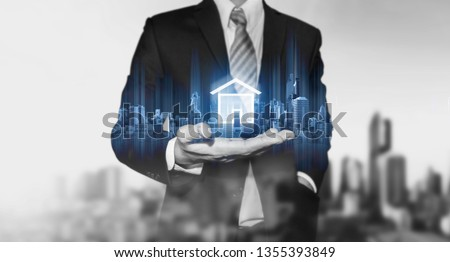 Businessman holding modern buildings hologram, and home icon. Real estate business, building technology and smart home concept #1355393849