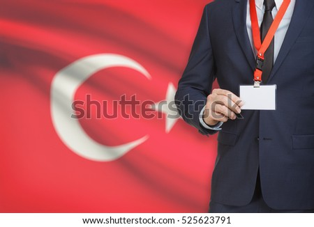 Businessman holding name card badge on a lanyard with a flag on background - Turkey