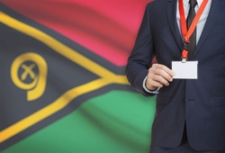 Businessman holding name card badge on a lanyard with a flag on background - Vanuatu
