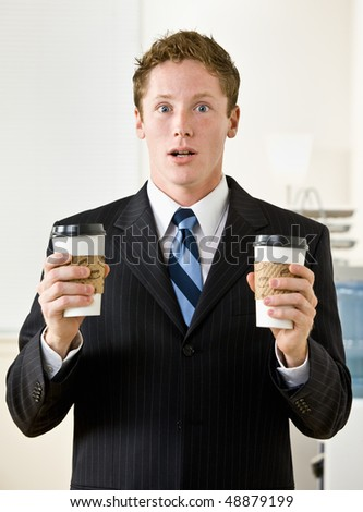 Businessman holding paper coffee cups