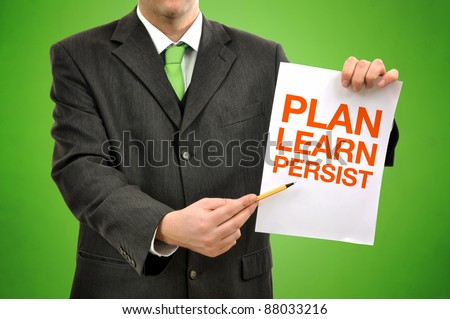 Businessman holding paper with printed marketing terminology. plan learn and persist.