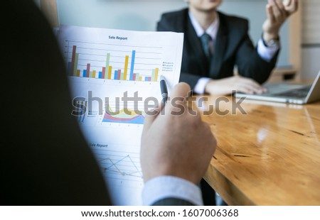 Businessman holding papers hands and smiling.Young team of coworkers making great business discussion in modern coworking office.