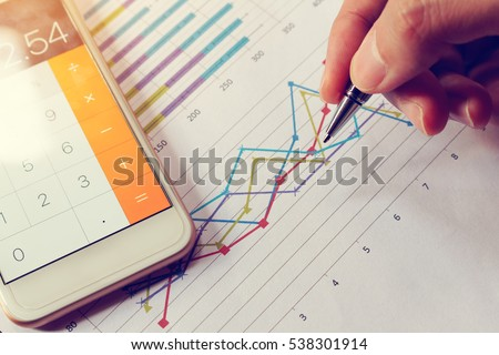 Businessman holding pen and think with cost with calculator in smartphone.