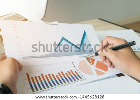Businessman holding pen for reading signing paperwork documents with report graph marketing or business reports in office.
