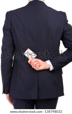 Businessman holding playing card behind his back.