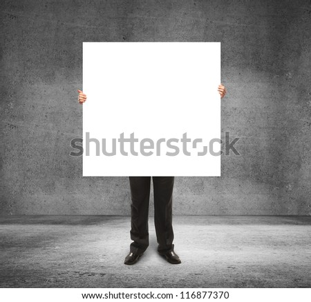 businessman holding poster in concrete room