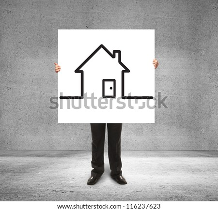 businessman holding poster with drawing house