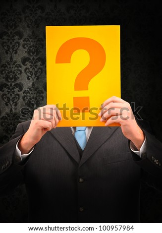 Businessman holding question mark in front of his head on vintage background
