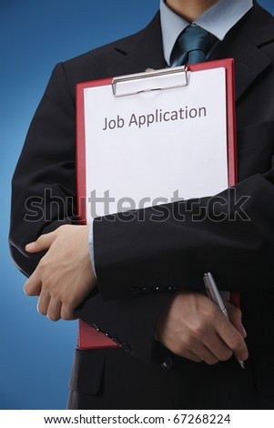 businessman holding resume and a pen