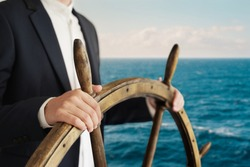 Businessman holding ship rudder and navigates in ocean.