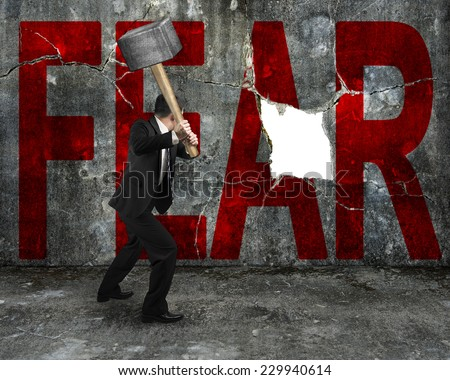 businessman holding sledgehammer hitting red FEAR word on concrete wall with large blank hole, overcoming fear concept.
