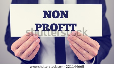 Businessman Holding Small White Signage Showing Non Profit Texts.