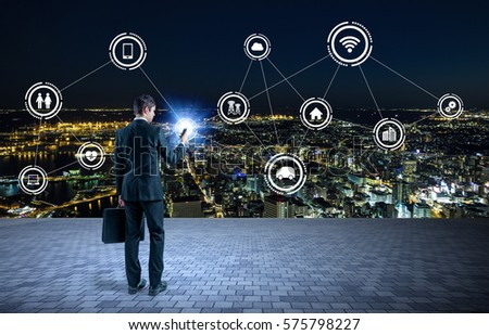 businessman holding smart phone and Internet of Things concept, smart city, wireless communication network, Information Communication Technology, abstract image visual #575798227