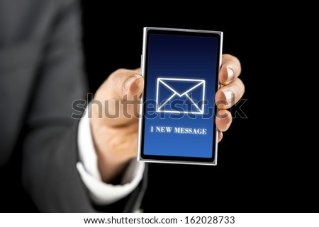 Businessman holding smartphone with 1 new message sign on screen. Over black background.