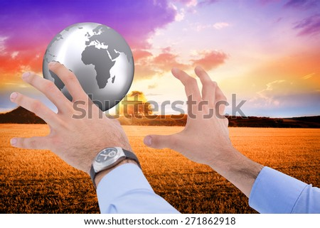 Businessman holding something with his hands against countryside scene
