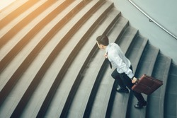 Businessman holding suitcase and running on stairs.