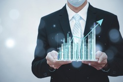 Businessman holding tablet bar graph of analytics and financial, Changes in new planning, Business growth, ideas and perspectives, Stock investment, and dividends yield from business in the new year