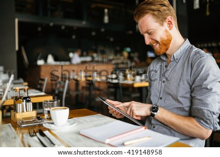 Businessman holding tablet in cafe