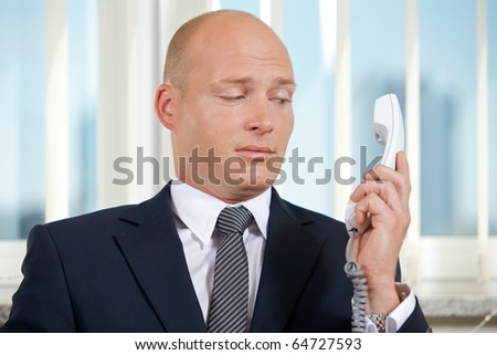 Businessman holding telephone receiver at office