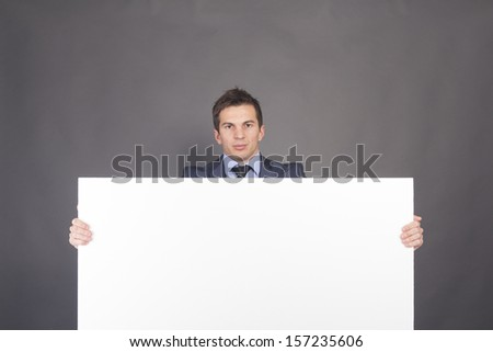 Businessman holding up a blank sign with room for adding text.