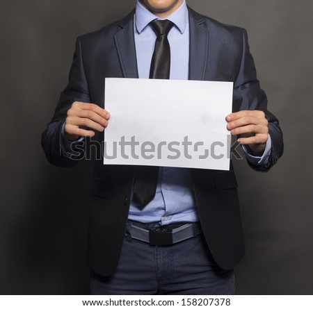 Businessman holding up a blank sign with room for adding text. Vertical shot. Isolated on gray.
