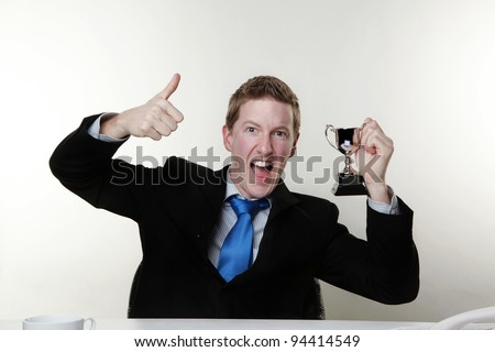 businessman holding up a cup medal to show that hes a winner