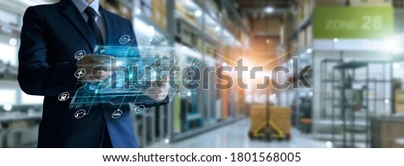 Businessman holding virtual interface panel of global logistics network distribution and transportation, Smart logistics, Innovation future of transport on large warehouse center background.