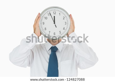 Businessman holding wall clock in front of face