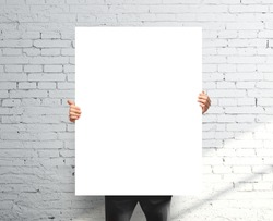 businessman holding white blank poster