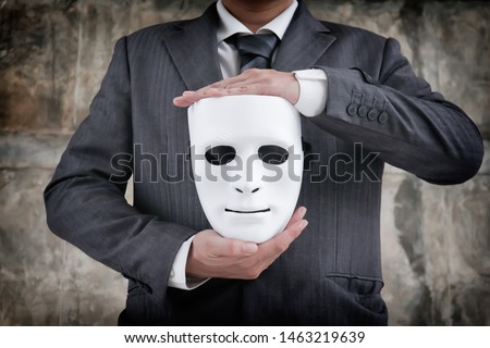Businessman holding white mask in his hand dishonest cheating agreement.Faking and betray business partnership concept