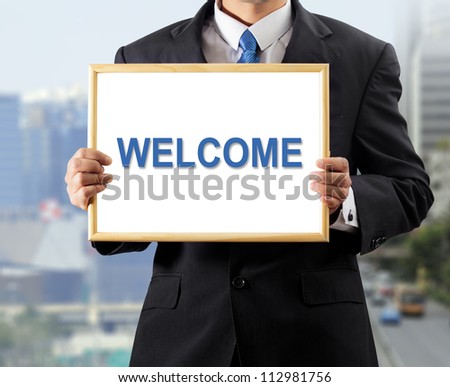 Businessman holding whiteboard with a message WELCOME