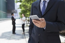 Businessman holding with cellphone at outdoor