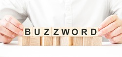 Businessman holding wooden block. Businessman watch on the wooden cubes with text BUZZWORD. financial market. financing