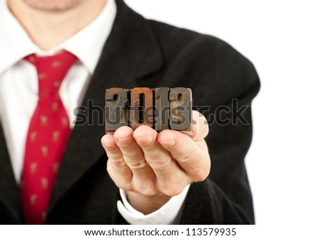 businessman holding year 2013 letterpress on white background