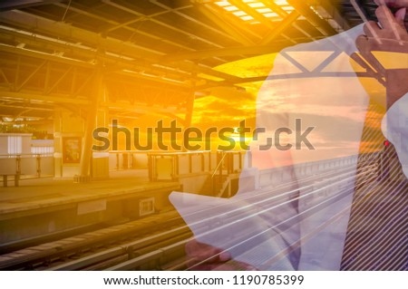 Businessman holds a tablet in his hand on a sky train station with sunlight Yellow evening ,With  concept of abstract Communicate over wireless networks and speed up competition. #1190785399