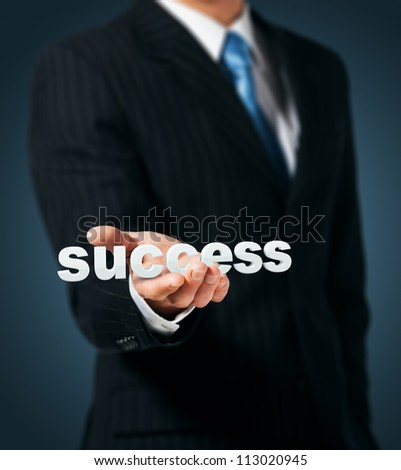 Businessman holds in a hand a word success