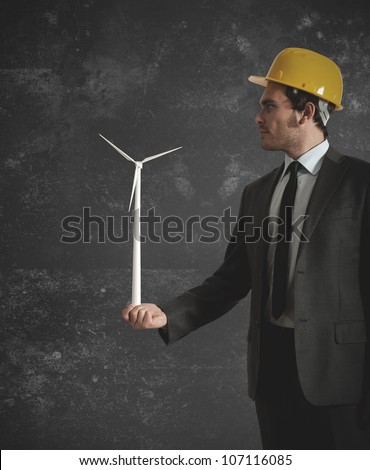 Businessman holds in hand a wind turbine