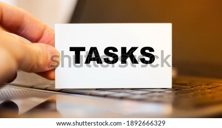 Businessman holds paper with TASKS on the background of a laptop before working day. Stock photo ©
