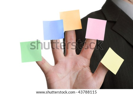 Businessman holds up five blank multi coloured stickies, one on each finger ready for text messages - stock photo