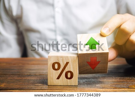 Businessman holds wooden blocks with percent and up or down arrow. Mortgage and loan rates. Interest rate, stocks, ranking. Business and finance concept.