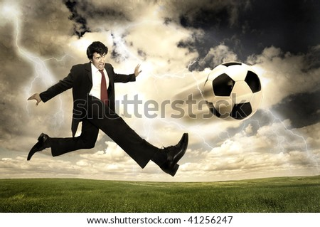 Businessman in a acrobatic pose kicking a ball in a stormy sky